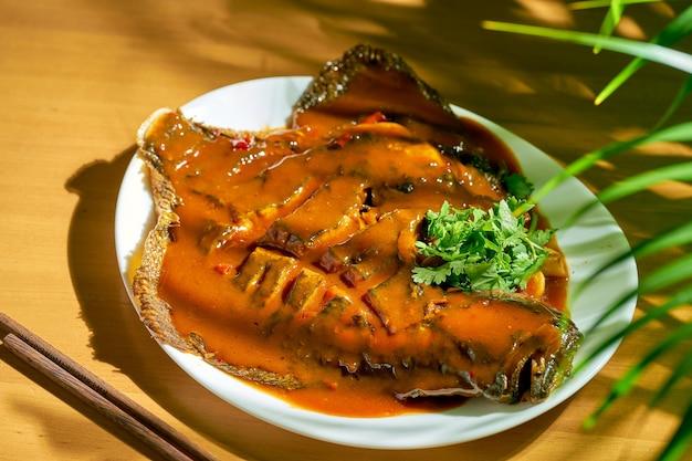 甘酸っぱいソースで揚げたスパイシーな丸ごとヒラメ。中華料理。