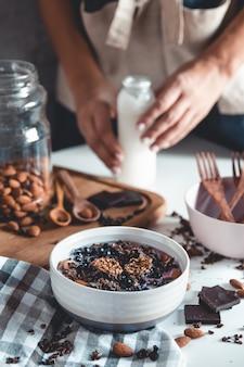 Острый йогурт с мюсли, сушеными ягодами, орехами, миндалем, специями (корица, анис) в чашке, тарелке.