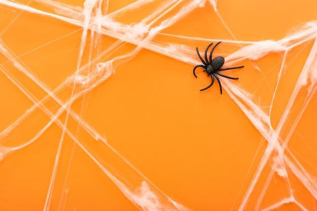 クモの巣とオレンジ色の背景にハロウィーンのシンボルとしてクモ。ハッピーハロウィン