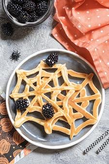 ハロウィーンの朝食のためのブラックベリーとクモの巣のパンケーキ