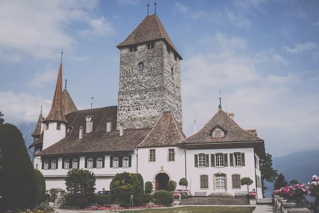 슈피츠, 스위스 - 2017년 6월 22일: 슈피츠 성 - 살아있는 박물관 및 공원, 스위스, 유럽에서 볼 수 있습니다. 국가적으로 중요한 스위스 문화유산입니다. 여름 풍경과 푸른 하늘