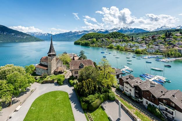 Замок spiez с туристическим судном на озере thun в берне, швейцарии.