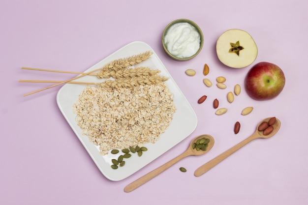 プレートに小麦とオーツ麦のフレークの小穂。テーブルの上の木のスプーン、カボチャの種とナッツ。リンゴの半分。フラットレイ。ピンクの背景 Premium写真