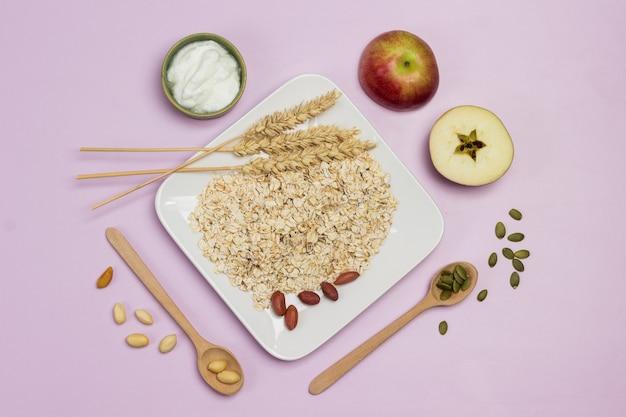 プレートに小麦とオーツ麦のフレークの小穂。テーブルの上の木のスプーン、カボチャの種とナッツ。リンゴの半分。フラットレイ。ピンクの背景
