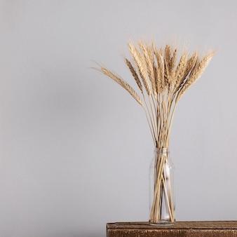 Колоски пшеницы в стеклянной вазе на сером фоне.