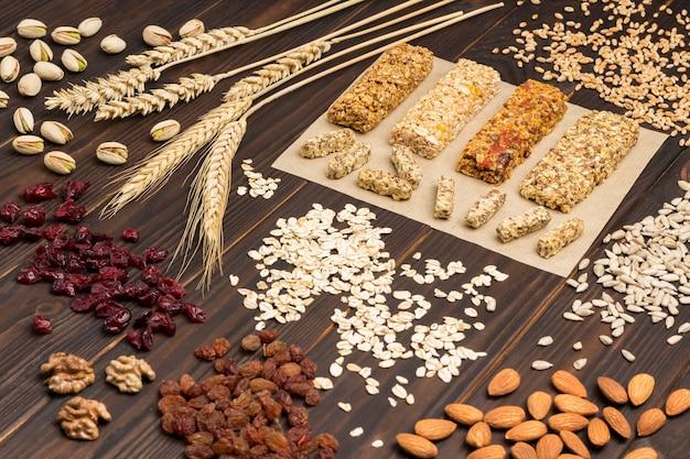 小麦、ナッツ、種子、シリアルの小穂。バランスの取れたプロテイングラノーラバー。ビーガンスナック、ダイエットレシピ。上面図。木の表面。閉じる