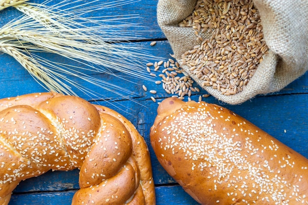 Spikelets of wheat, a bag of wheat and fresh bread on a blue surface.