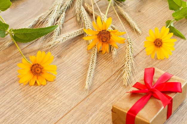 Spikelets of wheat, yellow flowers and gift box on wooden boards. top view.