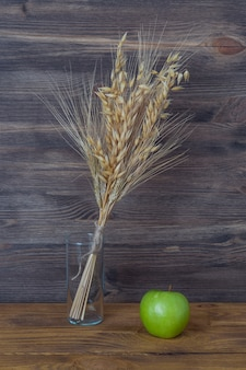 Spikes of wheat and barley in a vase on the background of wooden boards.