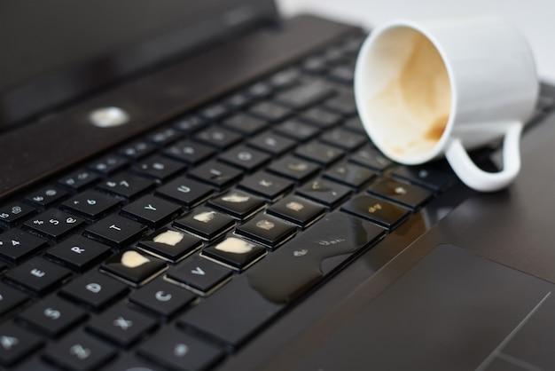 コンピューターのラップトップのキーボードの白いカップからコーヒーをこぼします。こぼれた液体によるコンピューターへの損傷