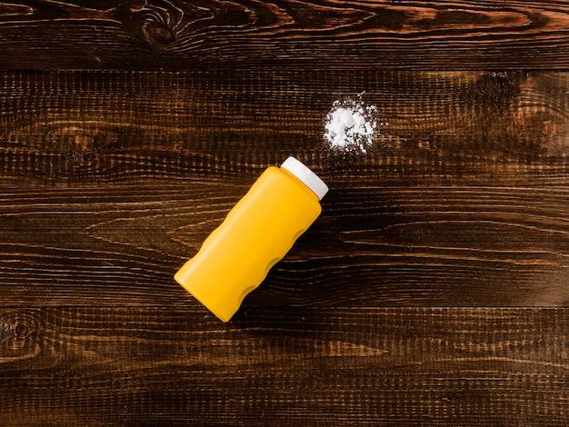 Spilled baby talcum powder on wooden background