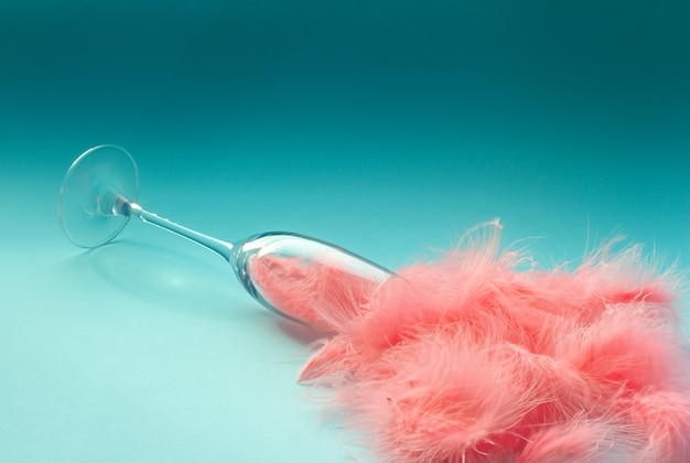 Spilled champagne glass full of pink feathers on a turquoise