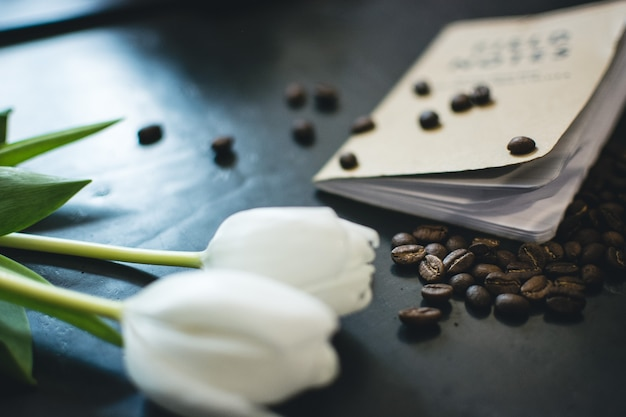 Spilled coffee beans, book and tulips