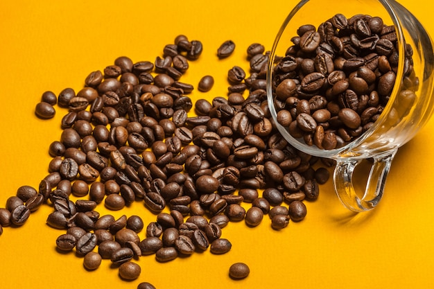 Spilled coffee beans on a bright yellow background