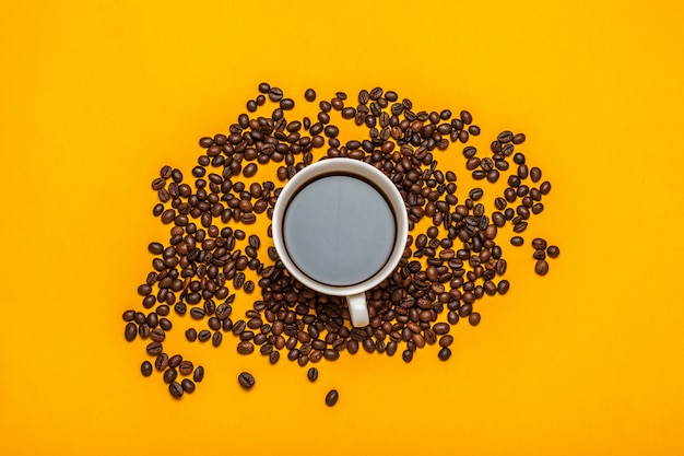 Spilled coffee beans on a bright yellow
