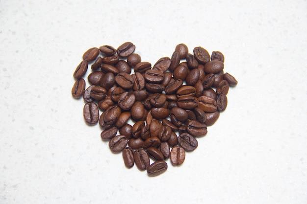 쏟 았된 커피 콩입니다. 마음의 형태로 커피입니다. 테이블에 커피 콩