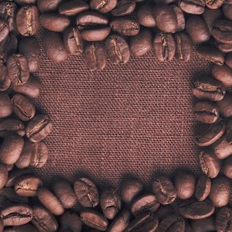 リネンテキスタイルの上にこぼれたコーヒー豆のフレーム