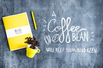 Spilled coffee beans from cup over the book big ideas and crayon with text on chalkboard