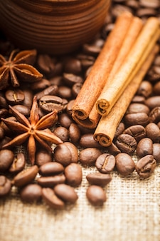 シナモンとアニスと粘土の手作りカップにこぼれたコーヒー豆