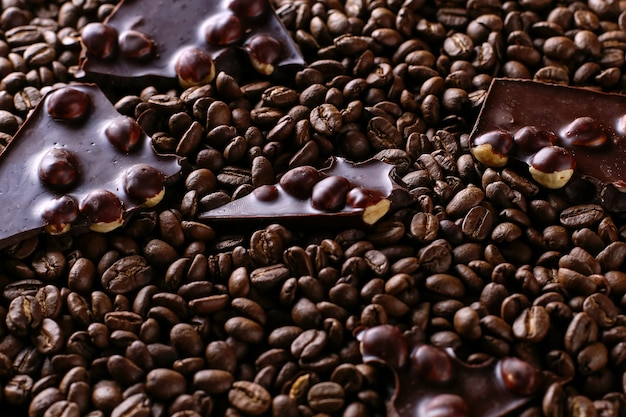 Spilled coffee grains and black chocolate, delicious background.