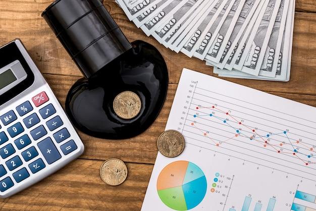 Разлитая сырая нефть, деньги, график и калькулятор на рабочем месте.