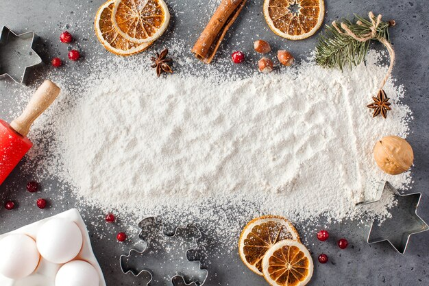 Spilled flour on a gray surface surrounded by rolling pin, spices