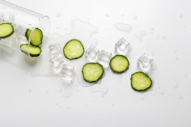 Spilled glass with refreshing water, cucumber slices and ice cubes on a light surface