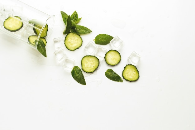 Spilled glass with refreshing water, cucumber slices, mint leave.