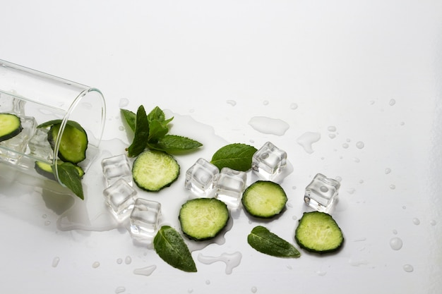 Spilled glass with refreshing water, cucumber slices, mint leaves and ice cubes on a light background
