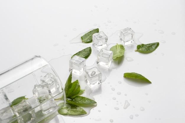 Пролитый стакан с освежающей водой, листьями мяты и кубиками льда на светлой поверхности
