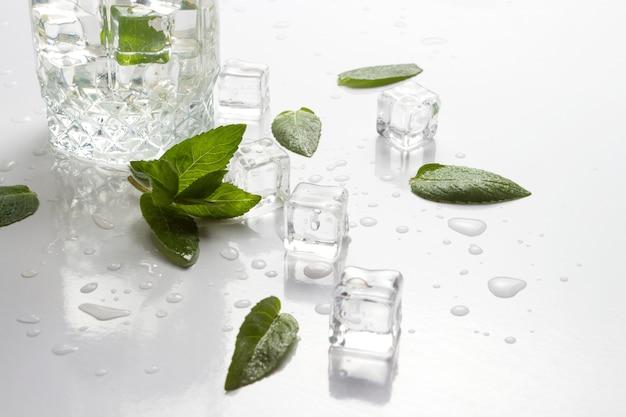 さわやかな水、ミントの葉、白い表面にアイスキューブとこぼれたガラス。フラットレイ、トップビュー