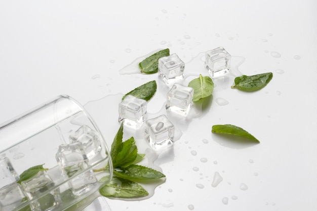Spilled glass with refreshing water, mint leaves and ice cubes on a light surface