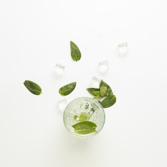 Spilled glass with refreshing water, mint leaves and ice cubes on white surface. flat lay, top veiw