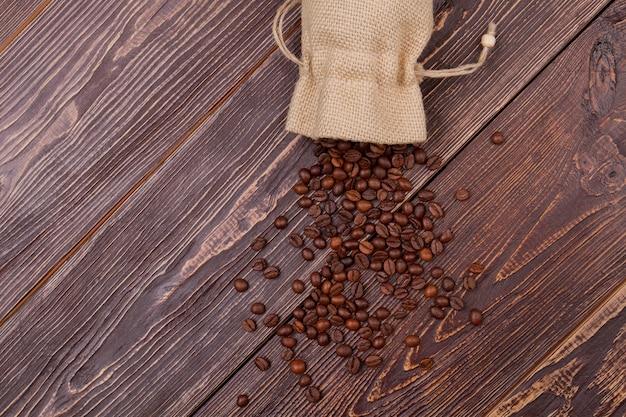 袋からコーヒー豆をこぼした。古い素朴な木の表面。上から見たトップ ビュー。