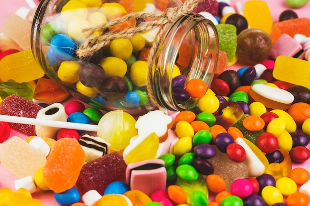 Spilled out colorful candies from glass jar