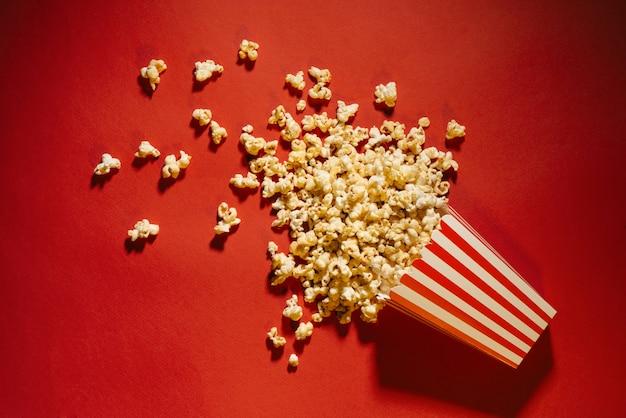 赤い背景、映画館、映画、エンターテインメントの概念にこぼれたポップコーン