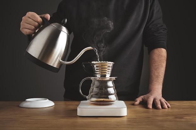 Проливает горячую воду для приготовления фильтрованного кофе из серебряного чайника в красивую прозрачную хромированную кофеварку на белых простых весах.