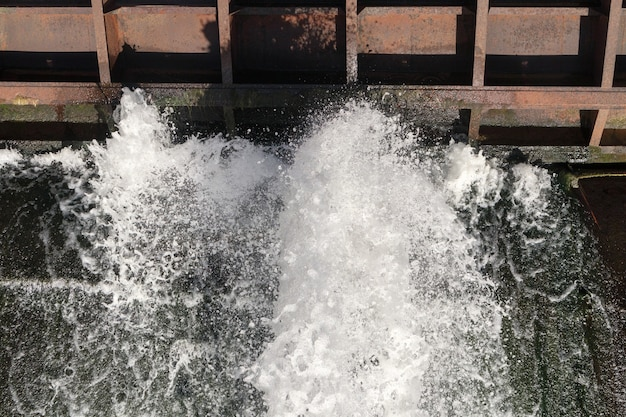 Spillway of old dam to regulate the water level in the river. top view of water spray through water gates in dam on the river on a sunny day.