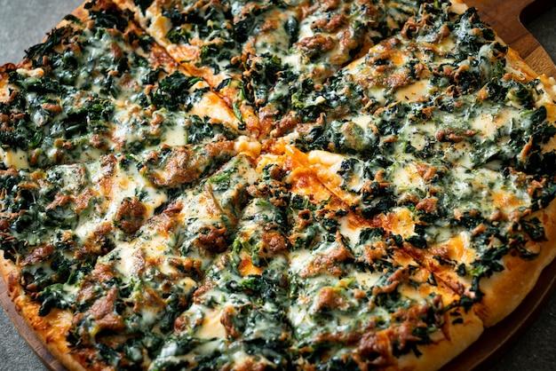 木製トレイにほうれん草とチーズのピザ-ビーガンとベジタリアンのフードスタイル