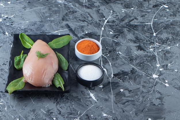 Шпинат и куриная грудка на блюде рядом с мисками для специй и соли, на мраморном фоне.