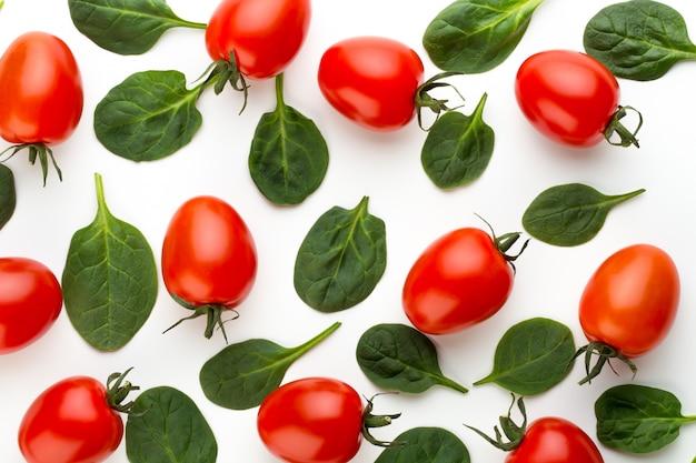 Шпинат и томатный узор на белом. вид сверху