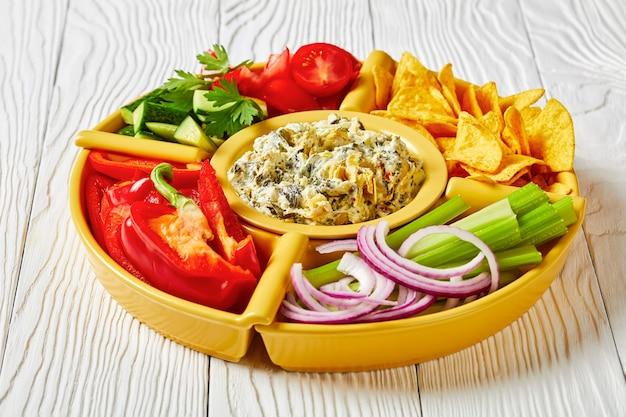 Дип-набор из шпината и артишока с чипсами тортилья, огурцом, палочками сельдерея, ломтиками помидора и красным болгарским перцем, пейзажный вид сверху, крупный план