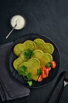 暗い背景の上の黒いプレートにギリシャヨーグルトソースとチェリートマトとハートの形をしたほうれん草のアボカドのパンケーキ。朝食の食べ物のコンセプト。コピースペースのある上面図。