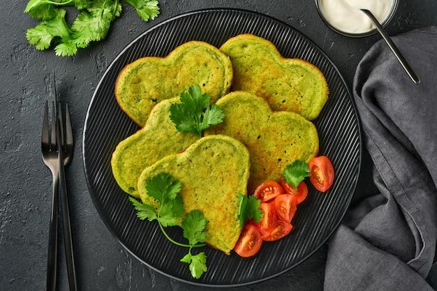 ハートの形をしたほうれん草のアボカドのパンケーキに、ギリシャヨーグルトソースとチェリートマトを黒のプレートに暗い背景の上に載せました。朝食の食べ物のコンセプト。コピースペースのある上面図。
