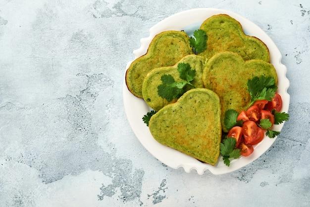 ハートの形をしたほうれん草のアボカドのパンケーキに、ギリシャヨーグルトソースとチェリートマトを白いプレートにライトグレーの背景に添えました。朝食の食べ物のコンセプト。コピースペースのある上面図。