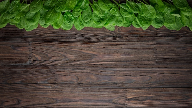 Spinach background of fresh and salty spinach leaves with copy space on a wooden table.