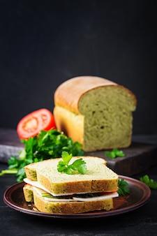 Хлеб со шпинатом и бутерброд с сыром, помидорами и зеленью. здоровый обед.