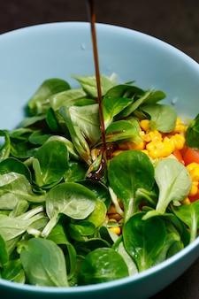 ほうれん草、とうもろこし、トマト、きゅうりのオリーブオイルサラダ。食べ物は適切な栄養です。ベジタリアンフード