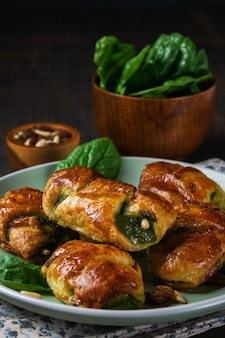 Spinach croissants with pinions and goat cheese and with a bowl of spinach on the plate.