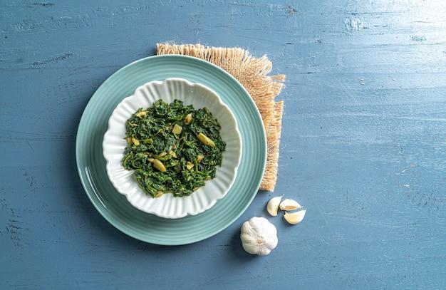白いボウルにほうれん草のカレーと青い木製のテーブルの上の青いプレート、ヴィンテージレイヤーの上面図